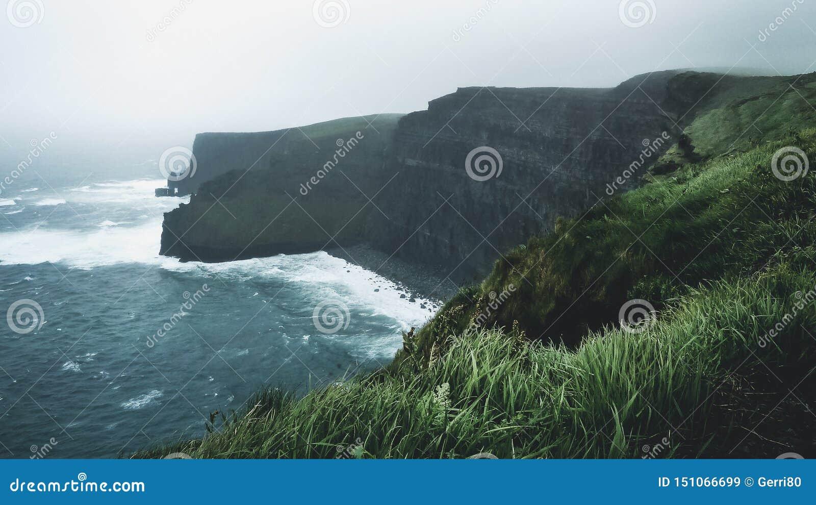 Fale rozbija na falezach Moher, na mglistym dniu w Irlandia