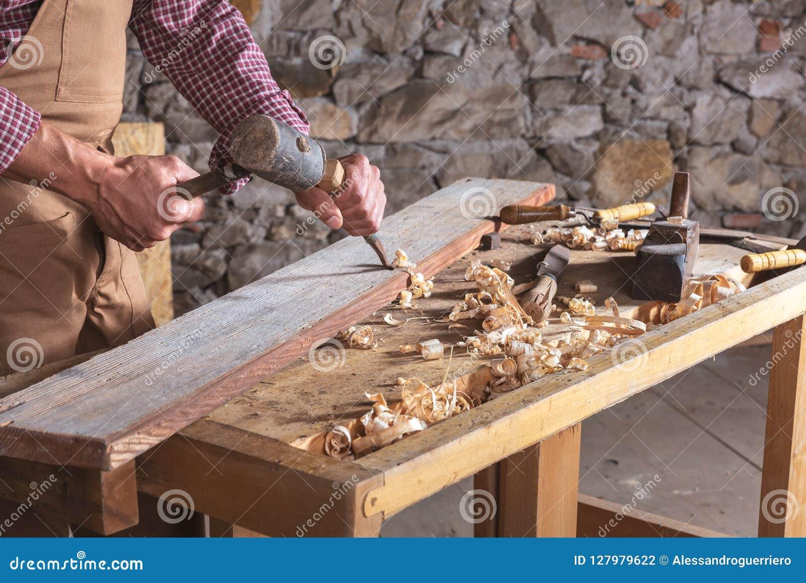 Falegname che per mezzo dello scalpello per lisciare giù legno