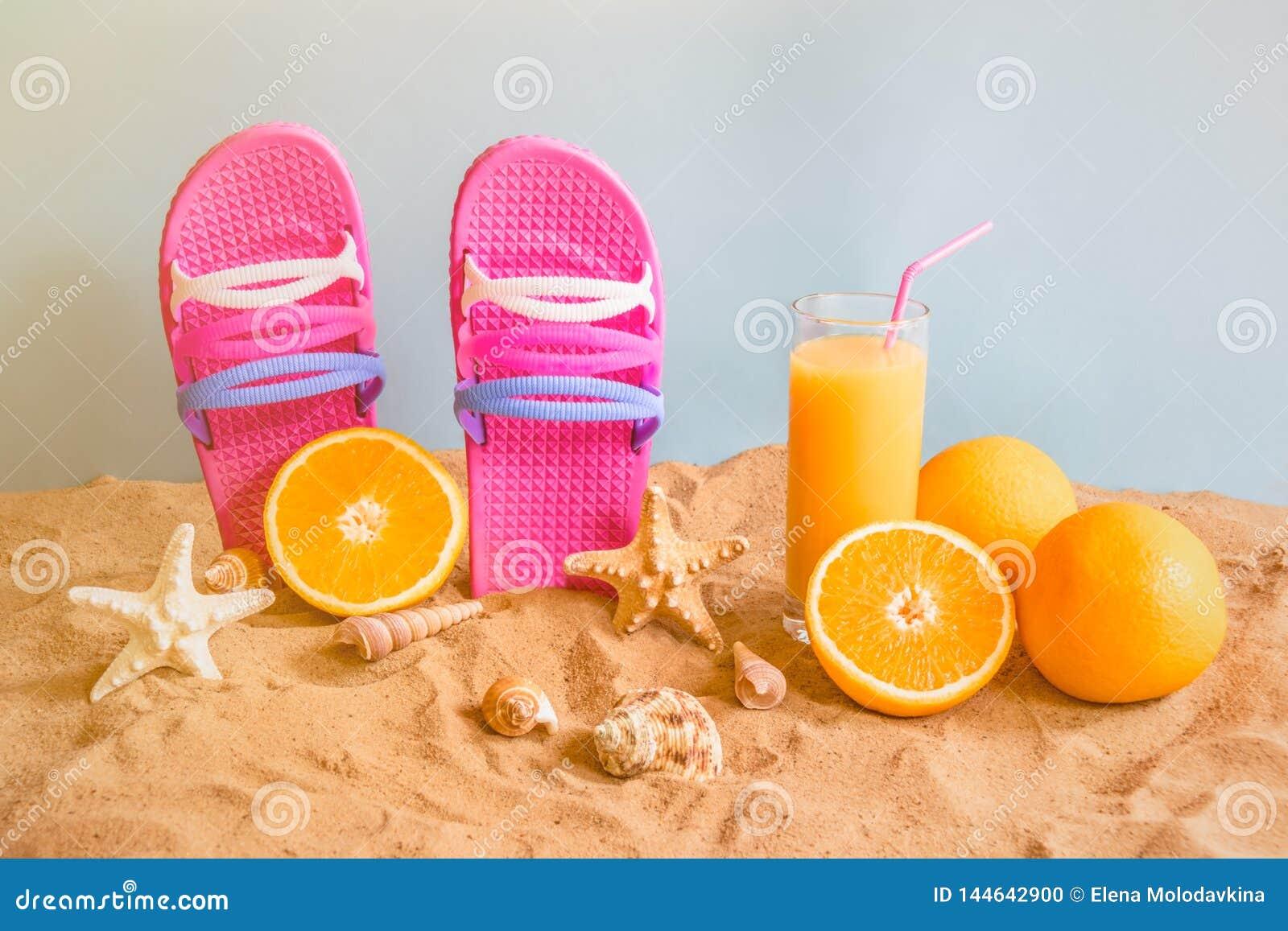 Falhanços de aleta, suco de laranja, laranjas, estrelas do mar e conchas do mar na praia da areia no contexto azul