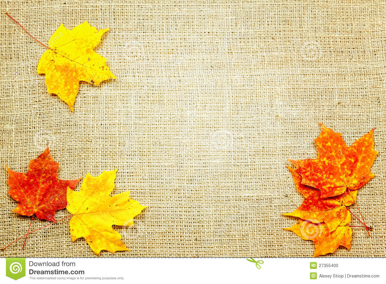 Fall-themed background of burlap and colorful leaves.