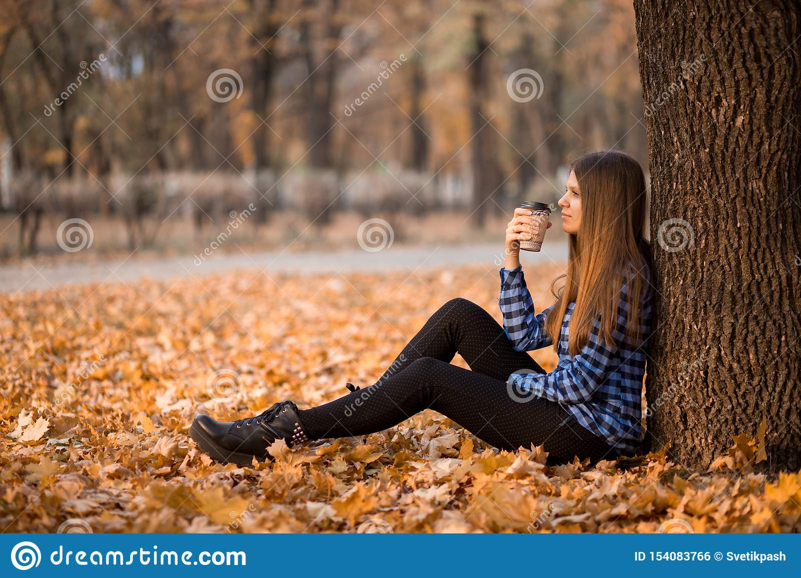 Fall concept. Happy and cheerful woman drinking coffee while sitting on park leaves under fall foliage.