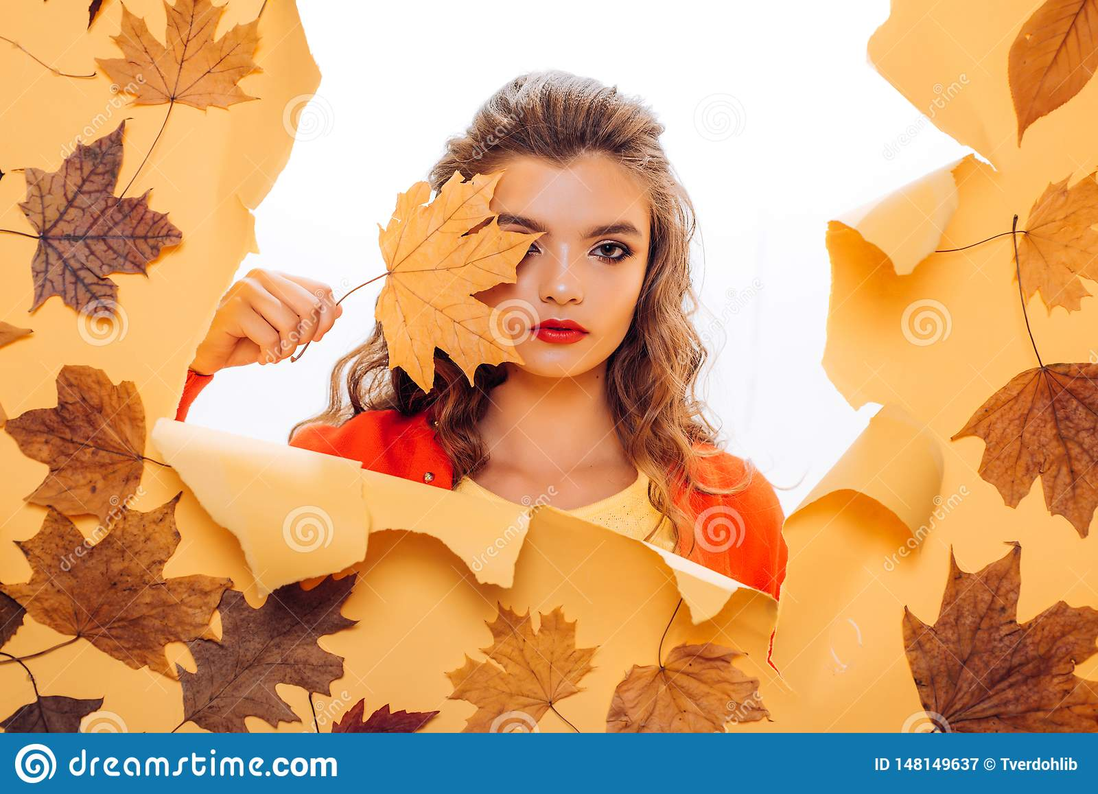 Fall look. Makeup girl peek through torn paper. Pretty girl cover face with autumn leaf. Young woman look out of hole