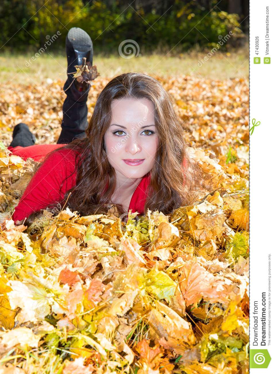 Fall. Portrait of beautiful young woman in autumn park with leaves