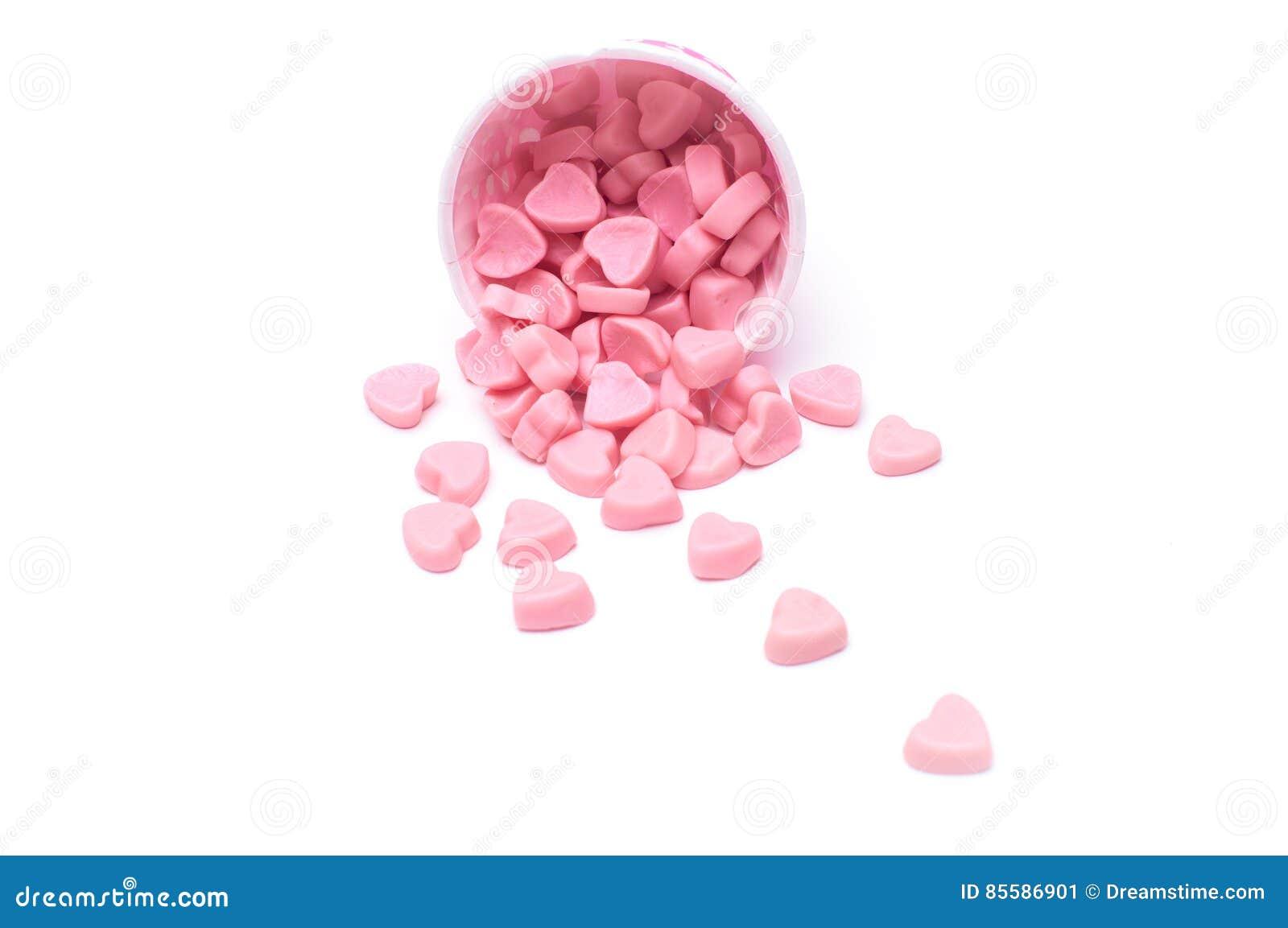Fallande hjärtagodis i isolerade pappers- koppar för rosa prick
