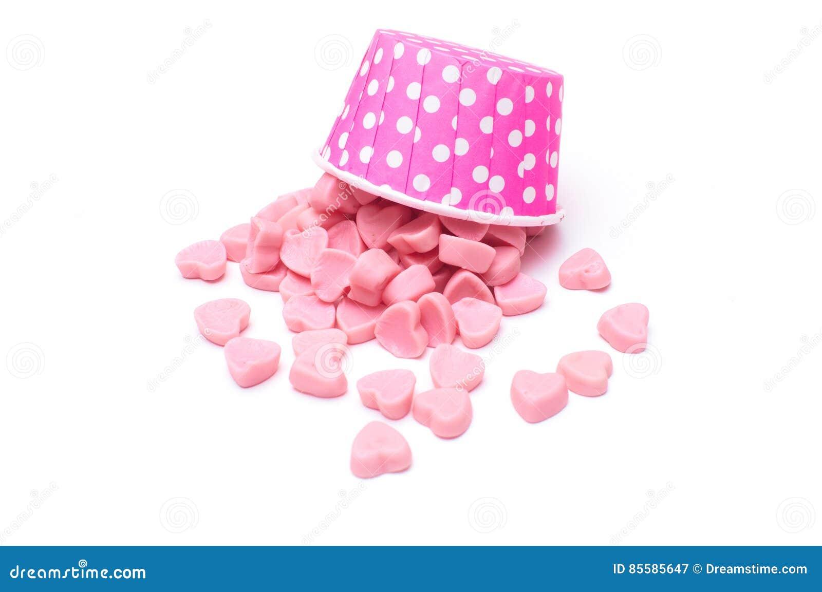 Fallande hjärtagodis i pappers- koppar för rosa prick