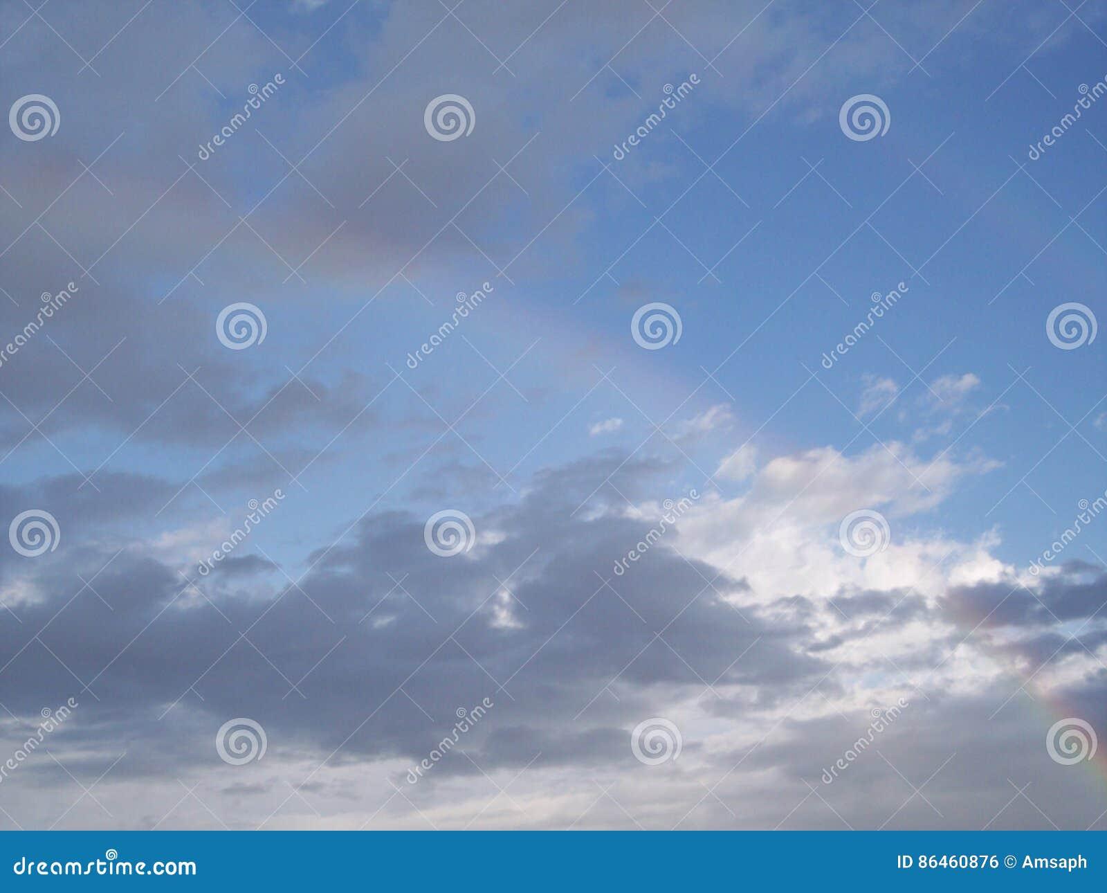Fallen doppelter Regenbogen gegen blauen Himmel und Wolken in Ohnmacht