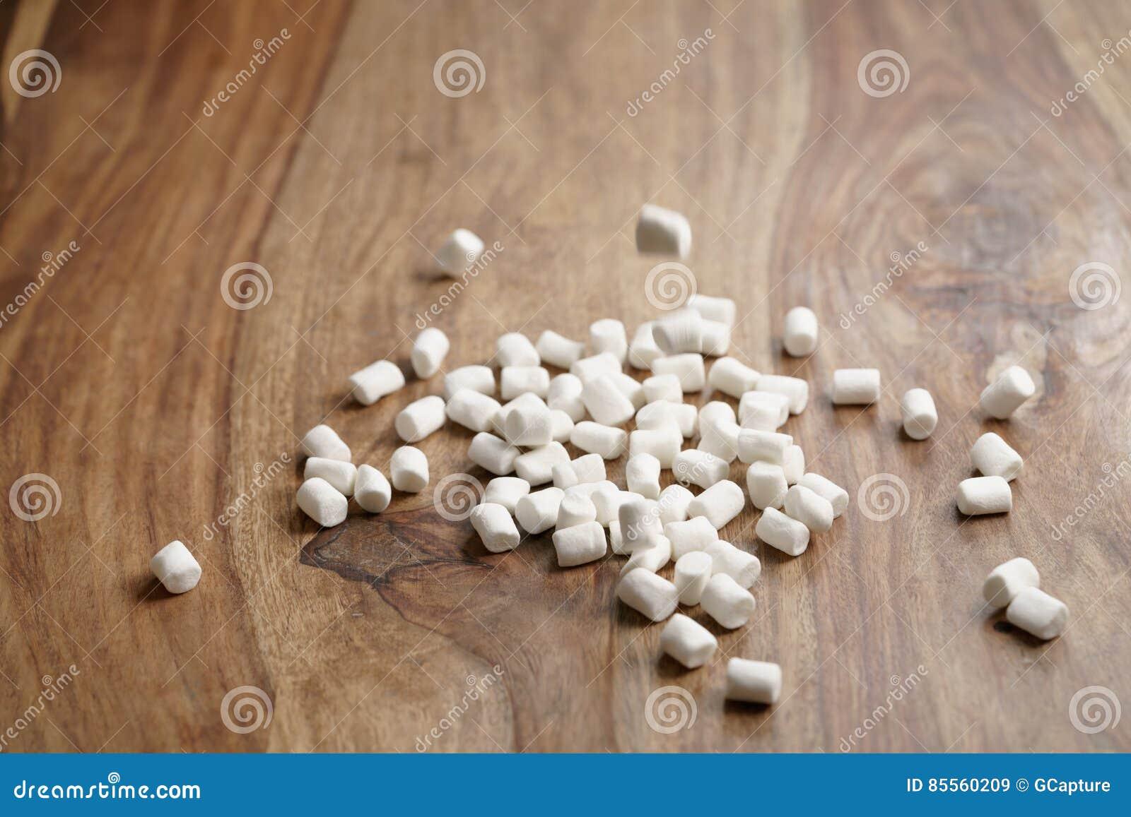 Fallende weiße Eibische auf Holztisch