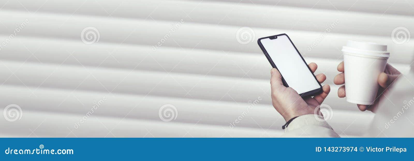 Falso para arriba de un smartphone y de una taza plástica con café en las manos de un individuo en un fondo blanco