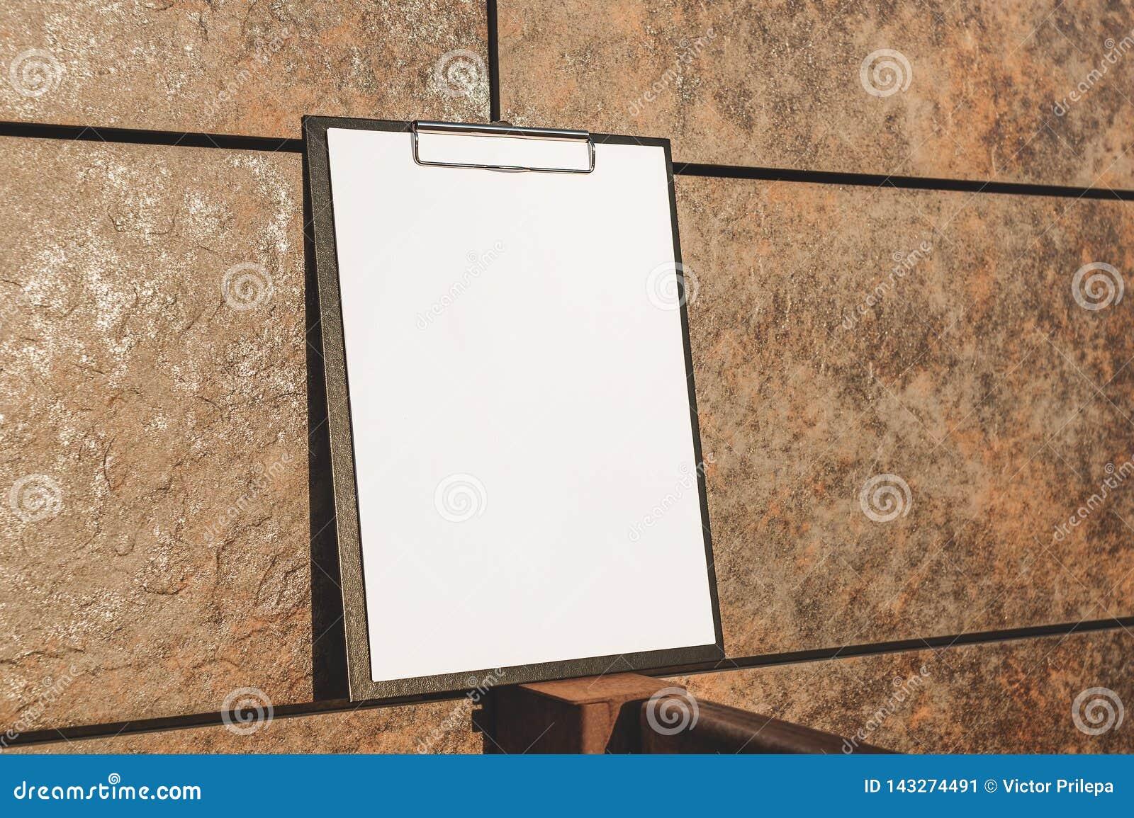 Falso su della compressa per la carta contro la parete
