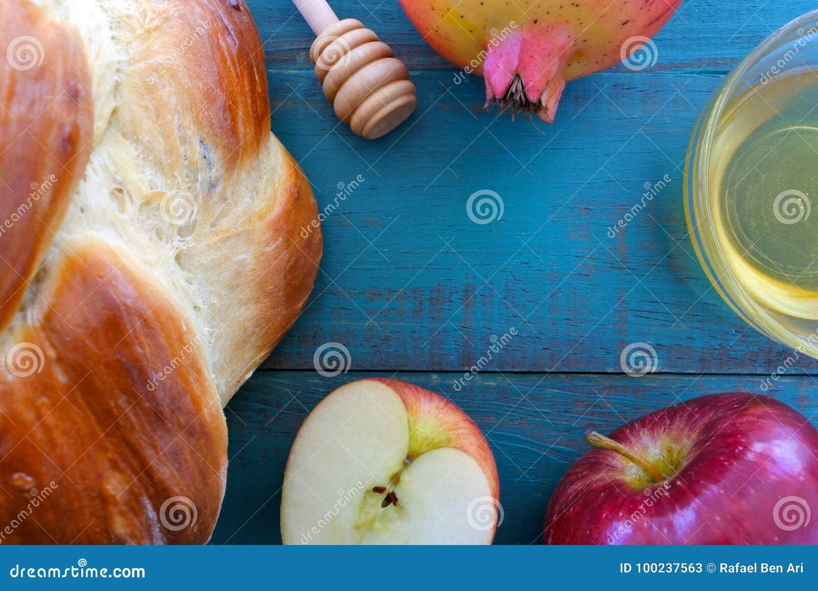 Falt lägger sikt av den runda söta challahen, honungkruset, det röda äpplet och p