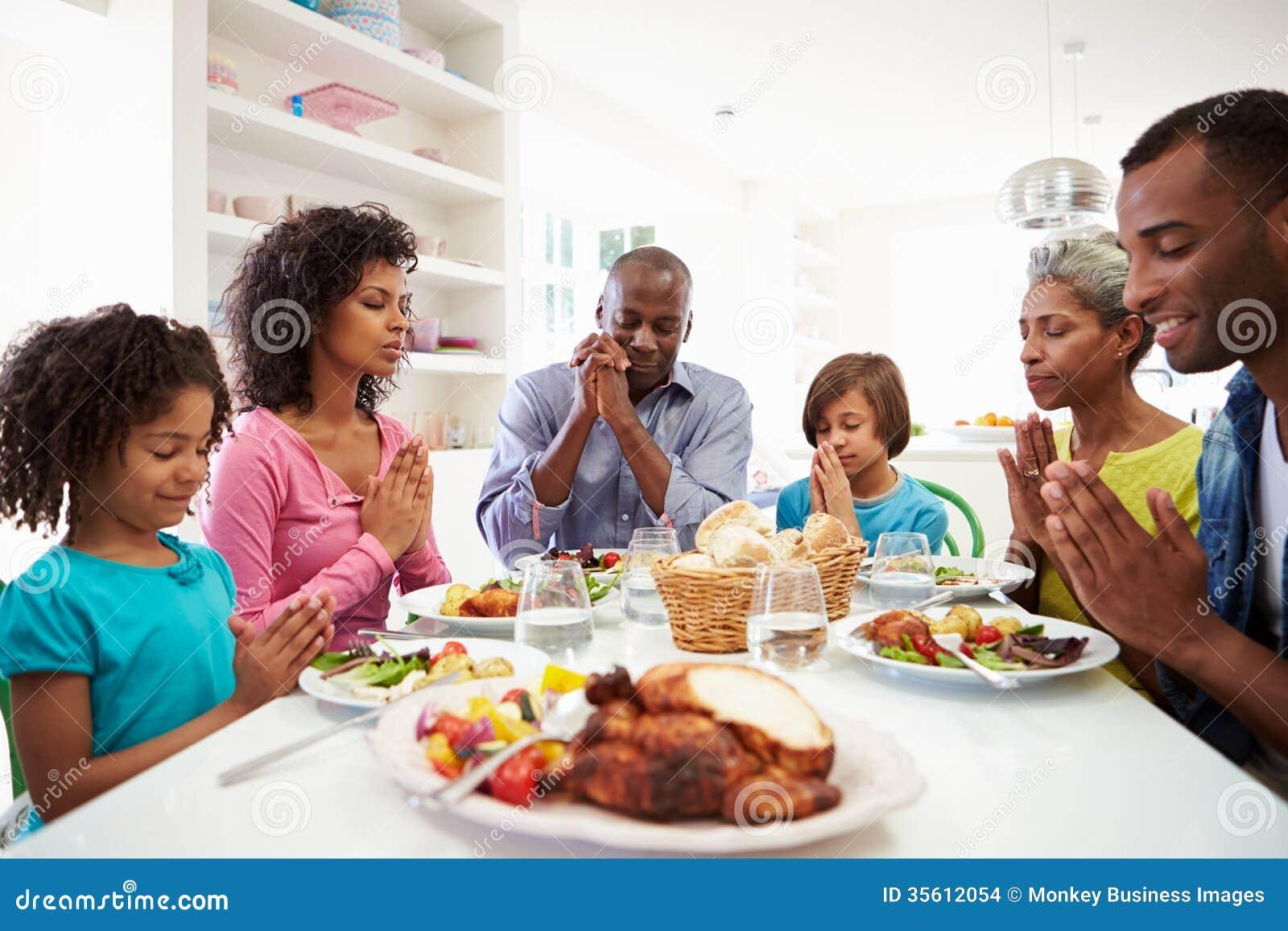 Família afro-americano da multi geração que reza em casa