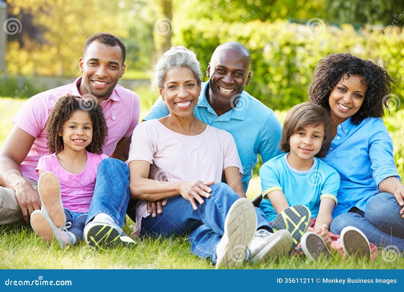 Família afro-americano da multi geração que senta-se no jardim