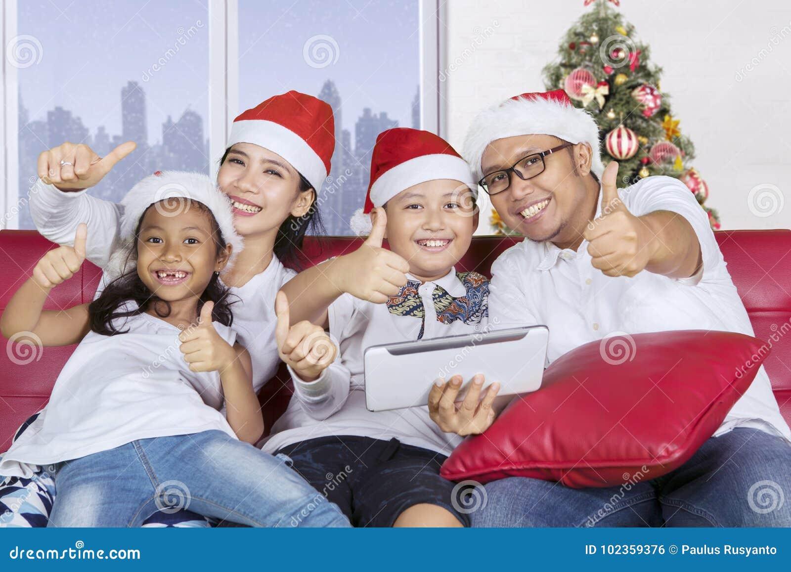 A família alegre com mostra do chapéu de Santa manuseia acima
