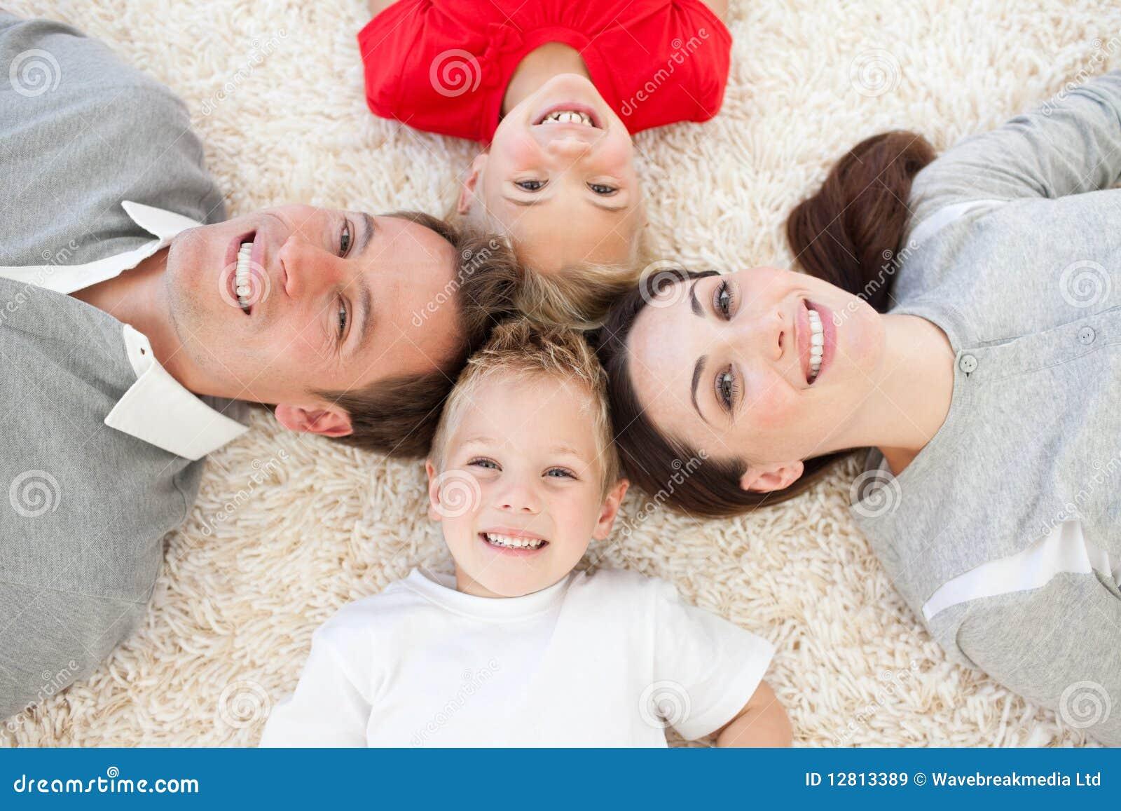 Família alegre que encontra-se no assoalho