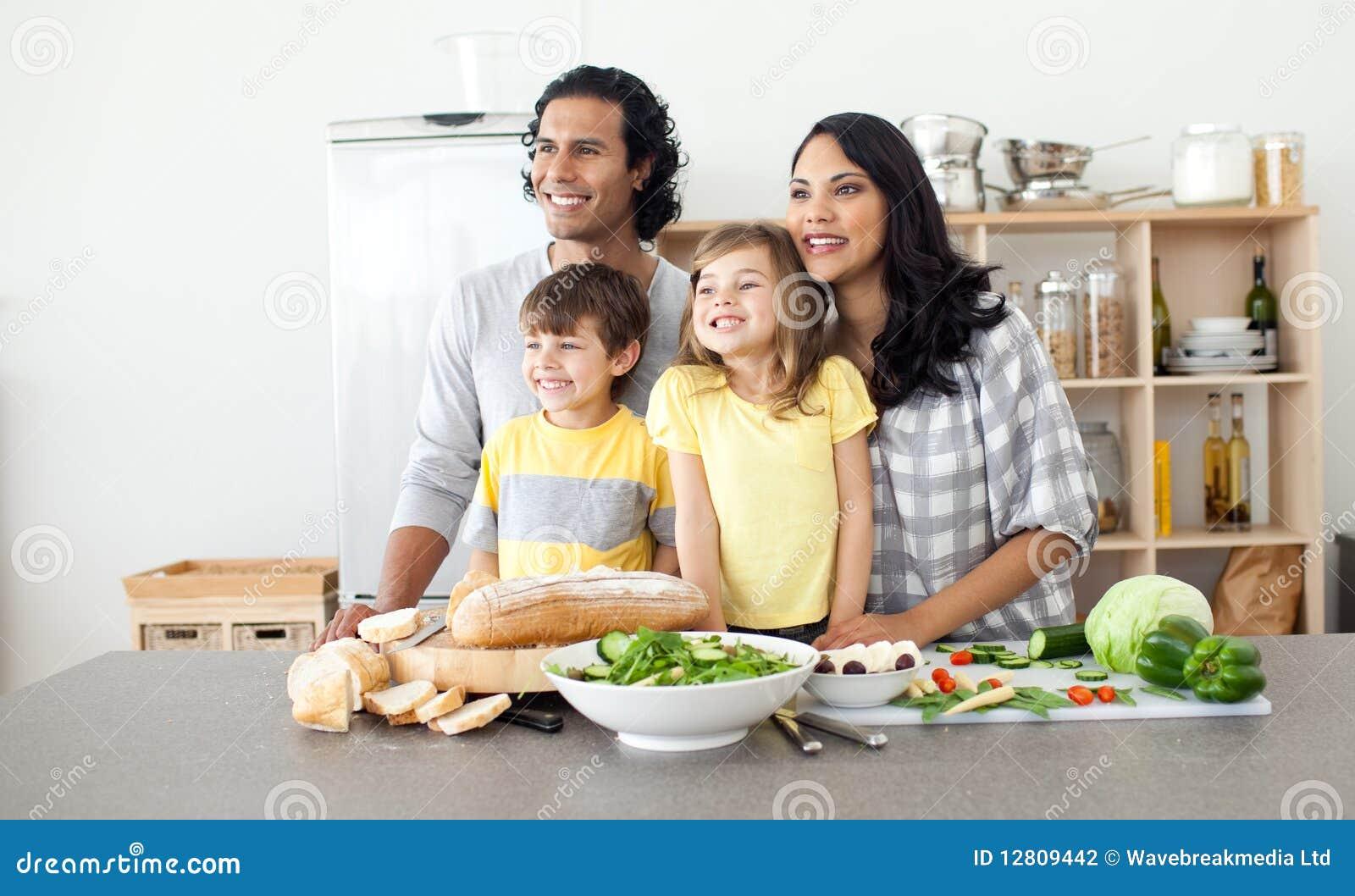 Família alegre que tem o divertimento na cozinha
