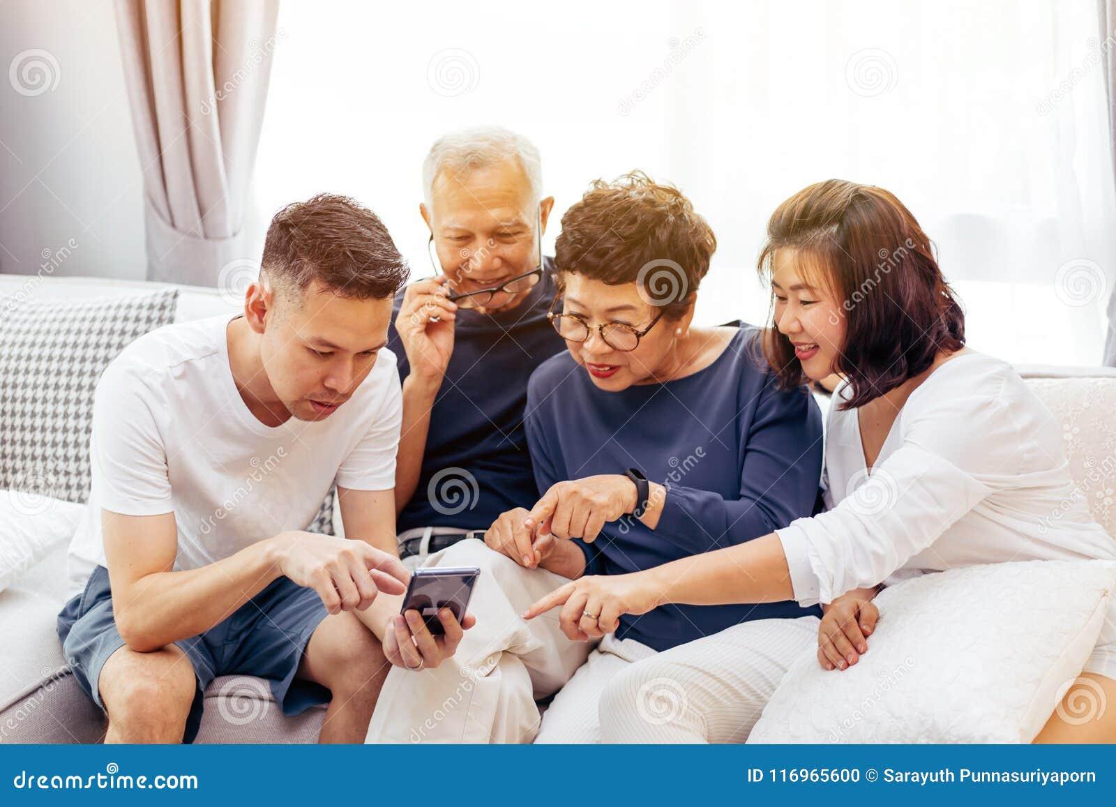 Família asiática com crianças adultas e os pais superiores que usam um telefone celular e relaxando em um sofá em casa junto