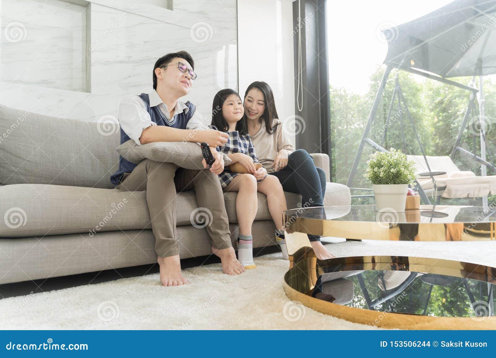 Família asiática feliz que olha a tevê junto no sofá na sala de visitas Fam?lia e conceito home