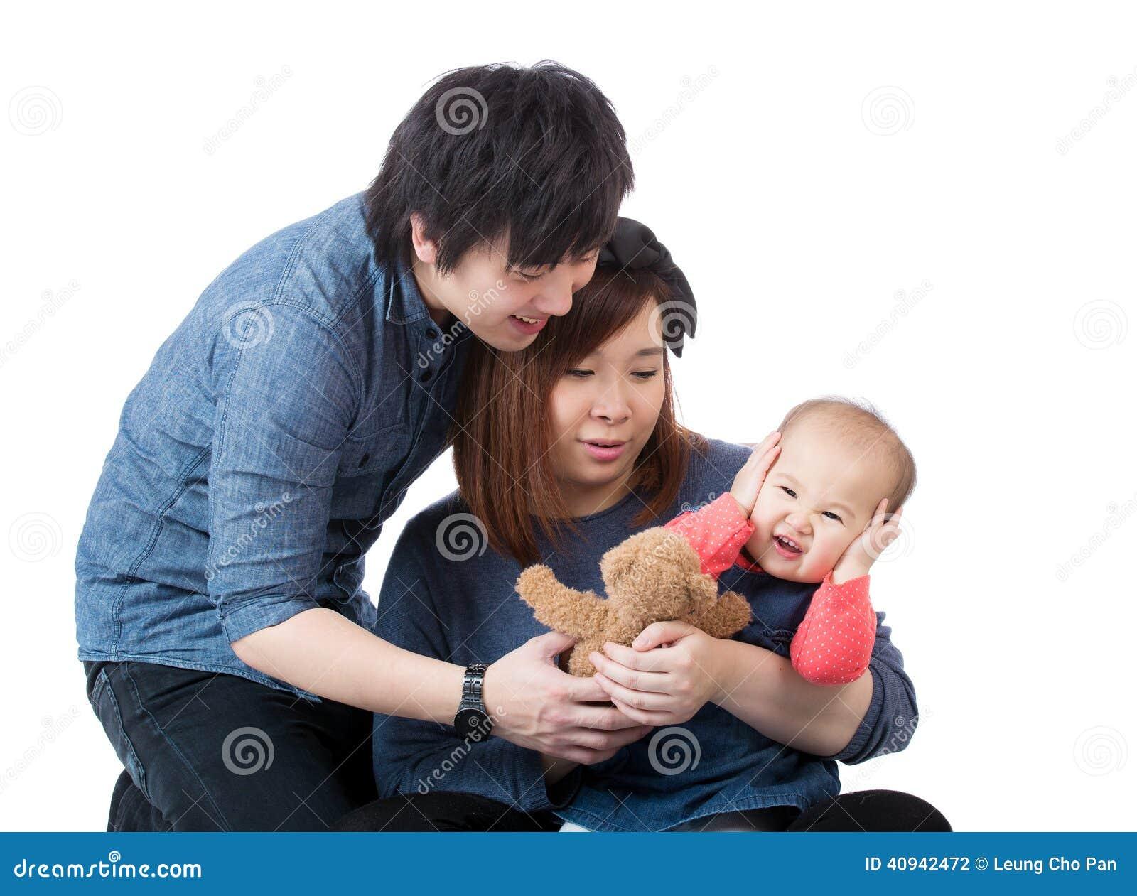 Família asiática que fala ao bebê da virada