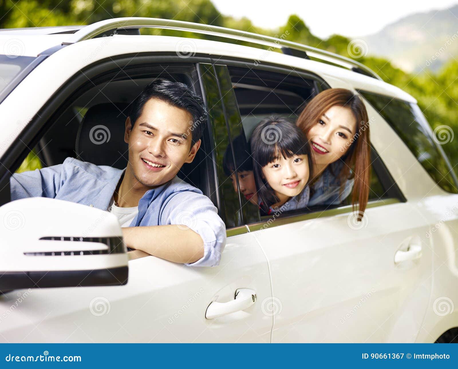 Família asiática que viaja pelo carro