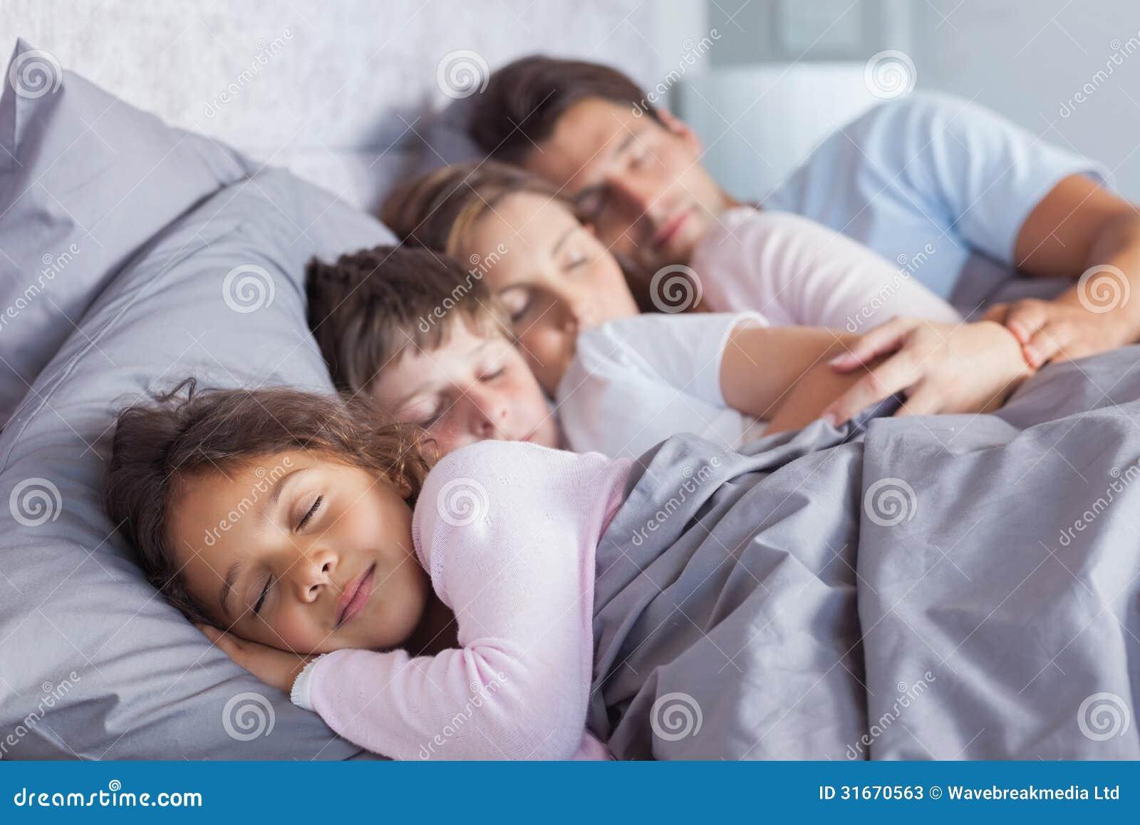 Família bonito que dorme na cama