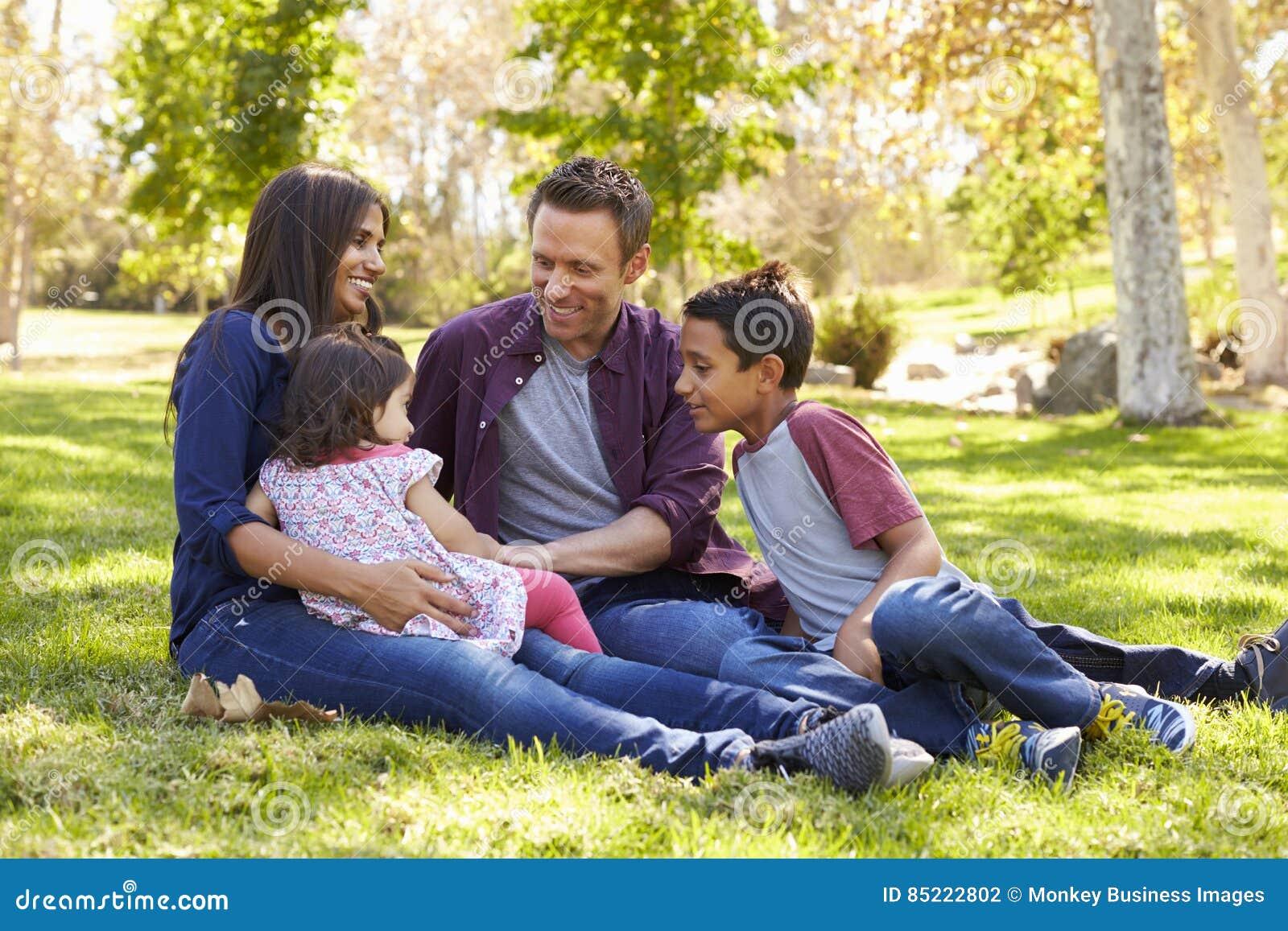 Família caucasiano asiática da raça misturada que senta-se na grama em um parque
