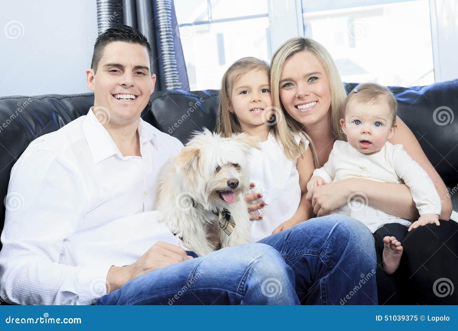 A família com animais de estimação senta-se no sofá em casa