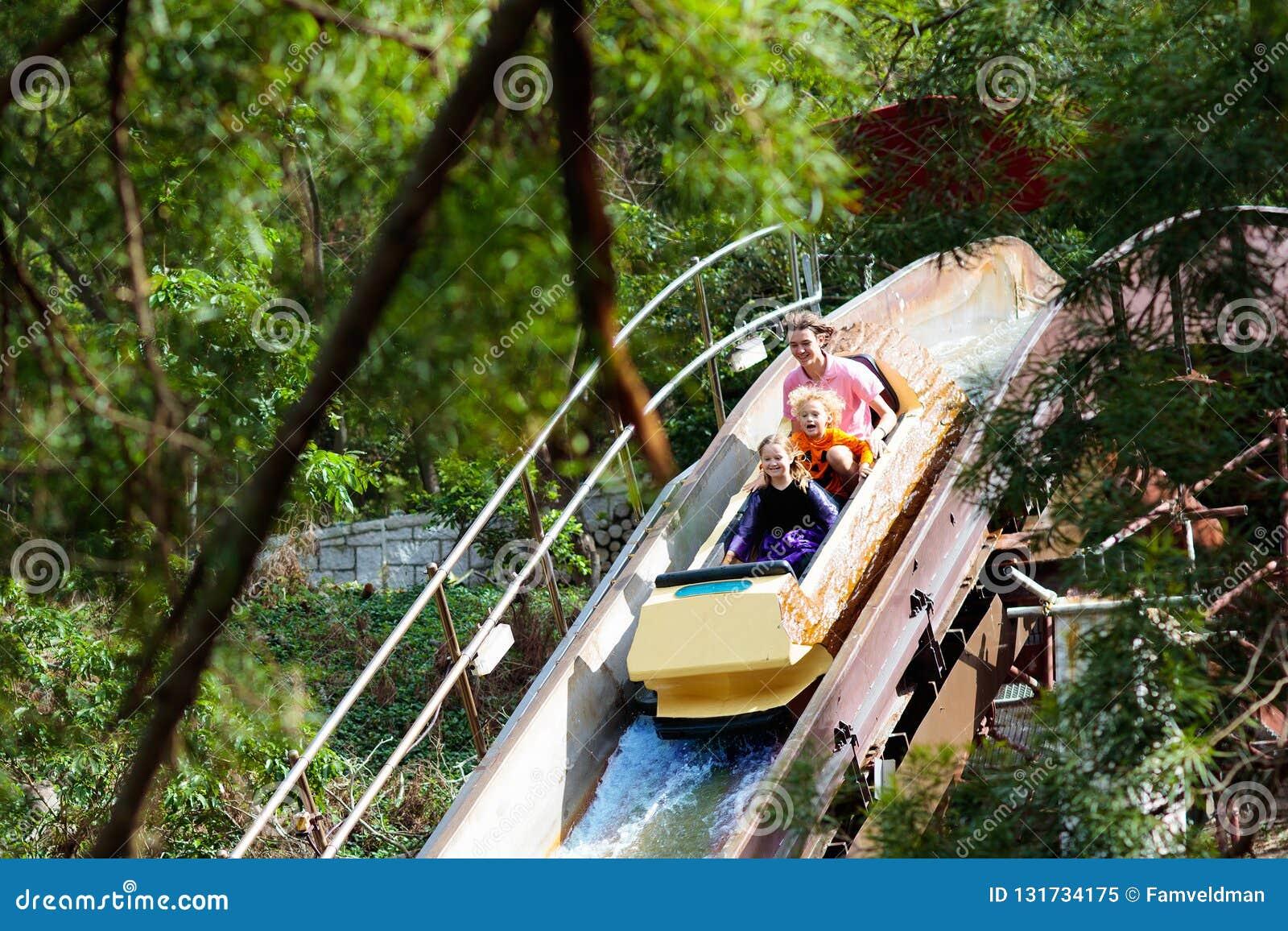 Família com as crianças na montanha russa no parque temático do divertimento Crianças que montam a atração de alta velocidade da
