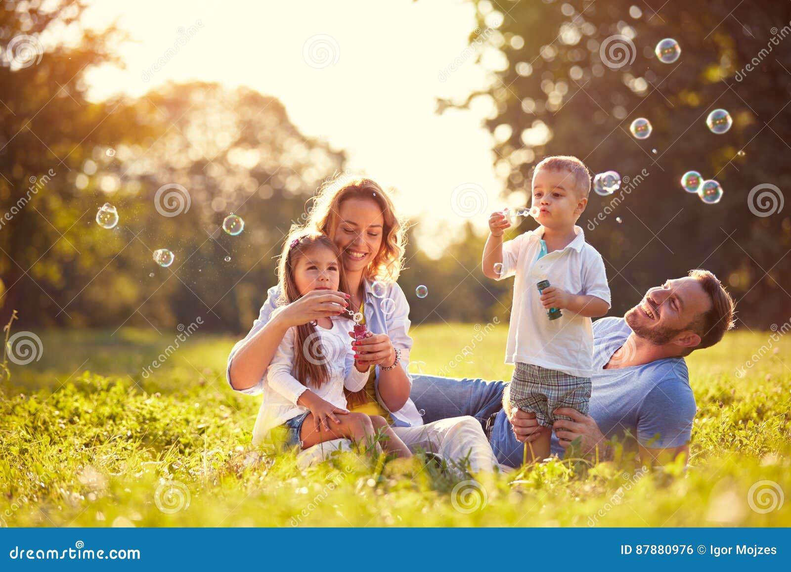 Família com bolhas de sabão do sopro das crianças