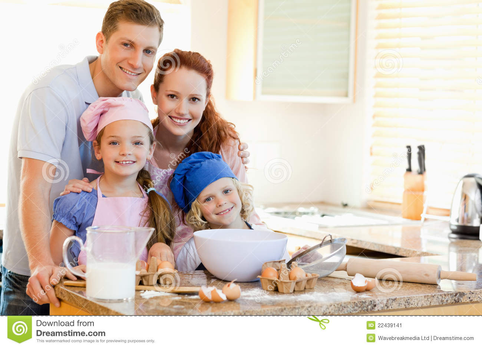 Família com os ingredientes do cozimento atrás do contador de cozinha