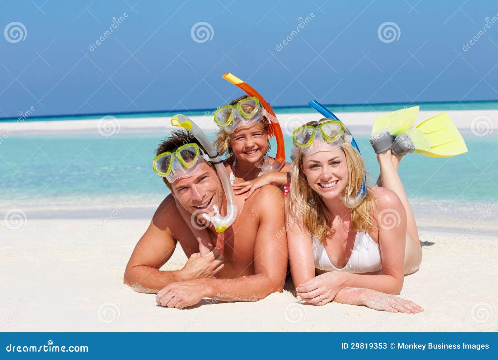 Família com Snorkels que aprecia o feriado da praia