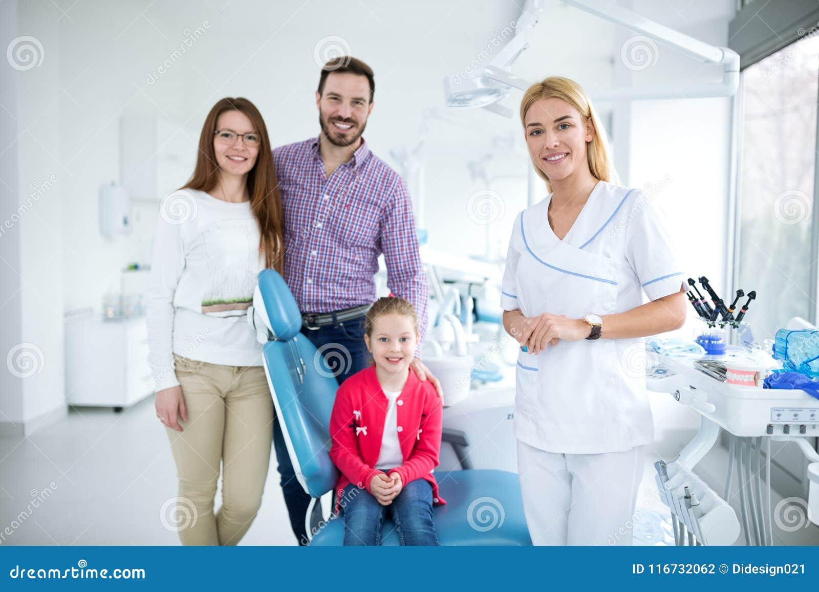 Família com um dentista novo de sorriso