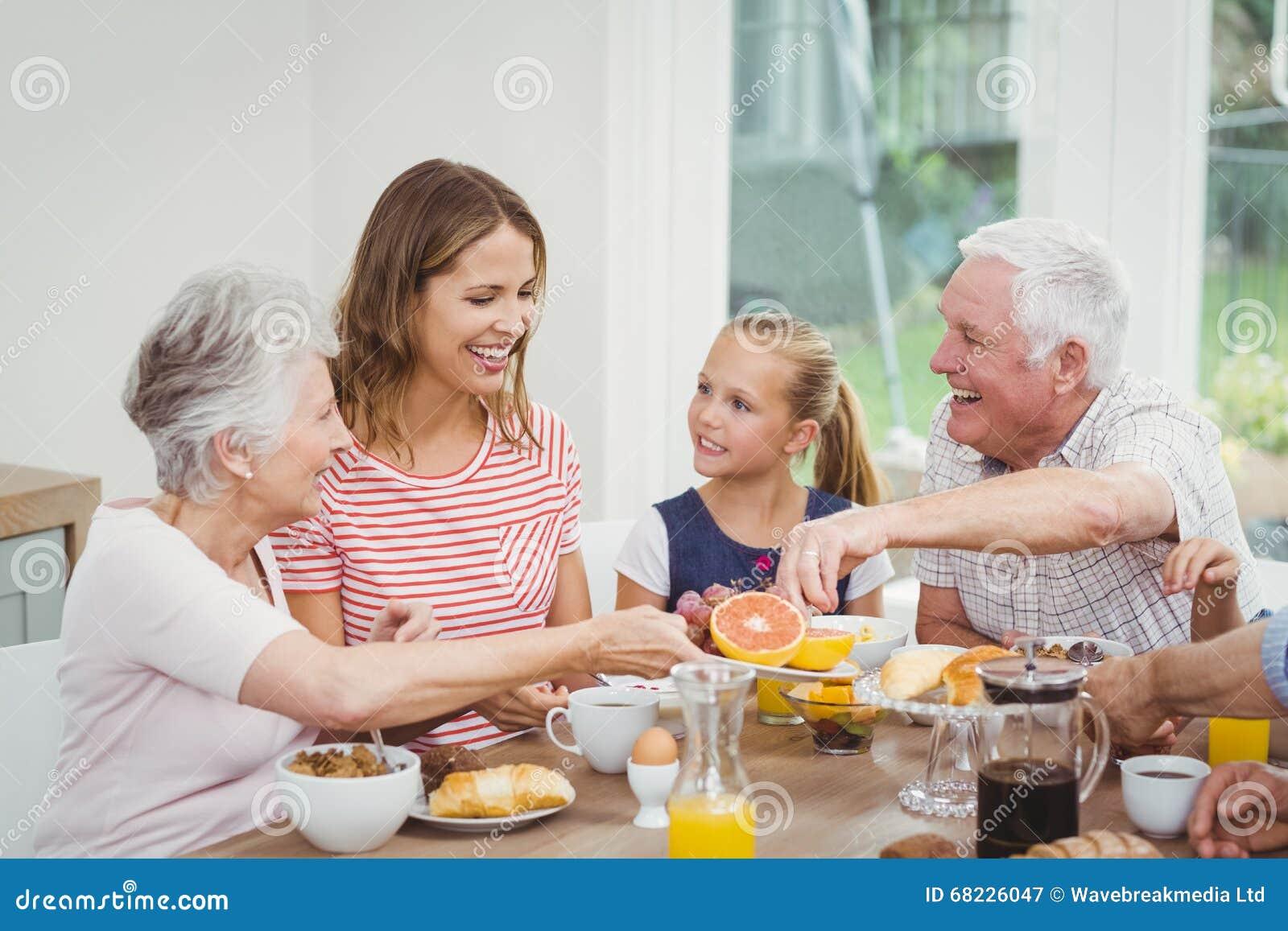 Família da Multi-geração que come frutos durante o café da manhã