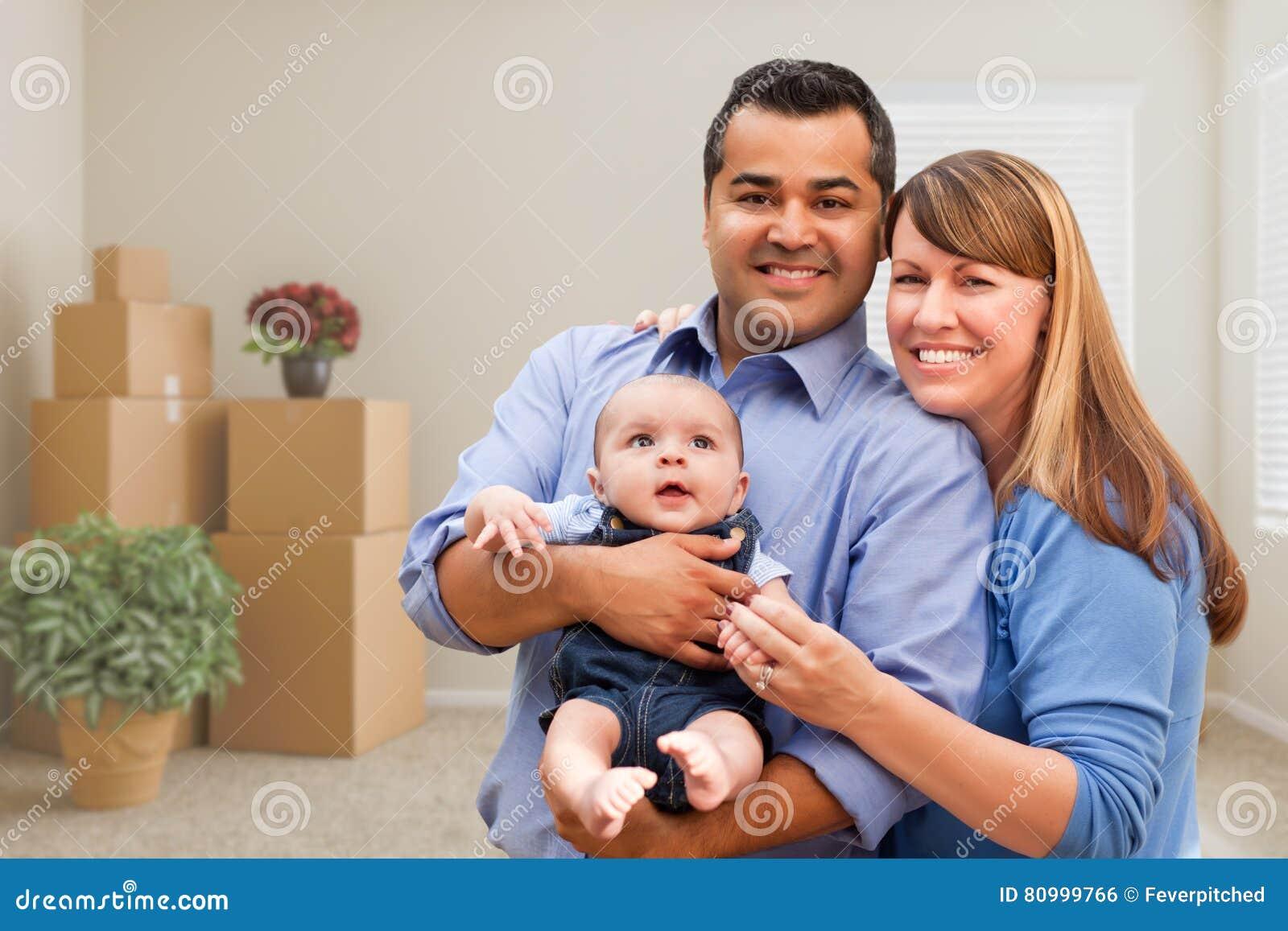 Família da raça misturada com o bebê na sala com as caixas moventes embaladas