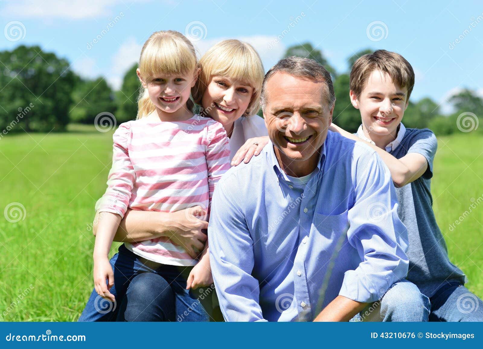 Família de quatro pessoas alegre em um dia ensolarado brilhante