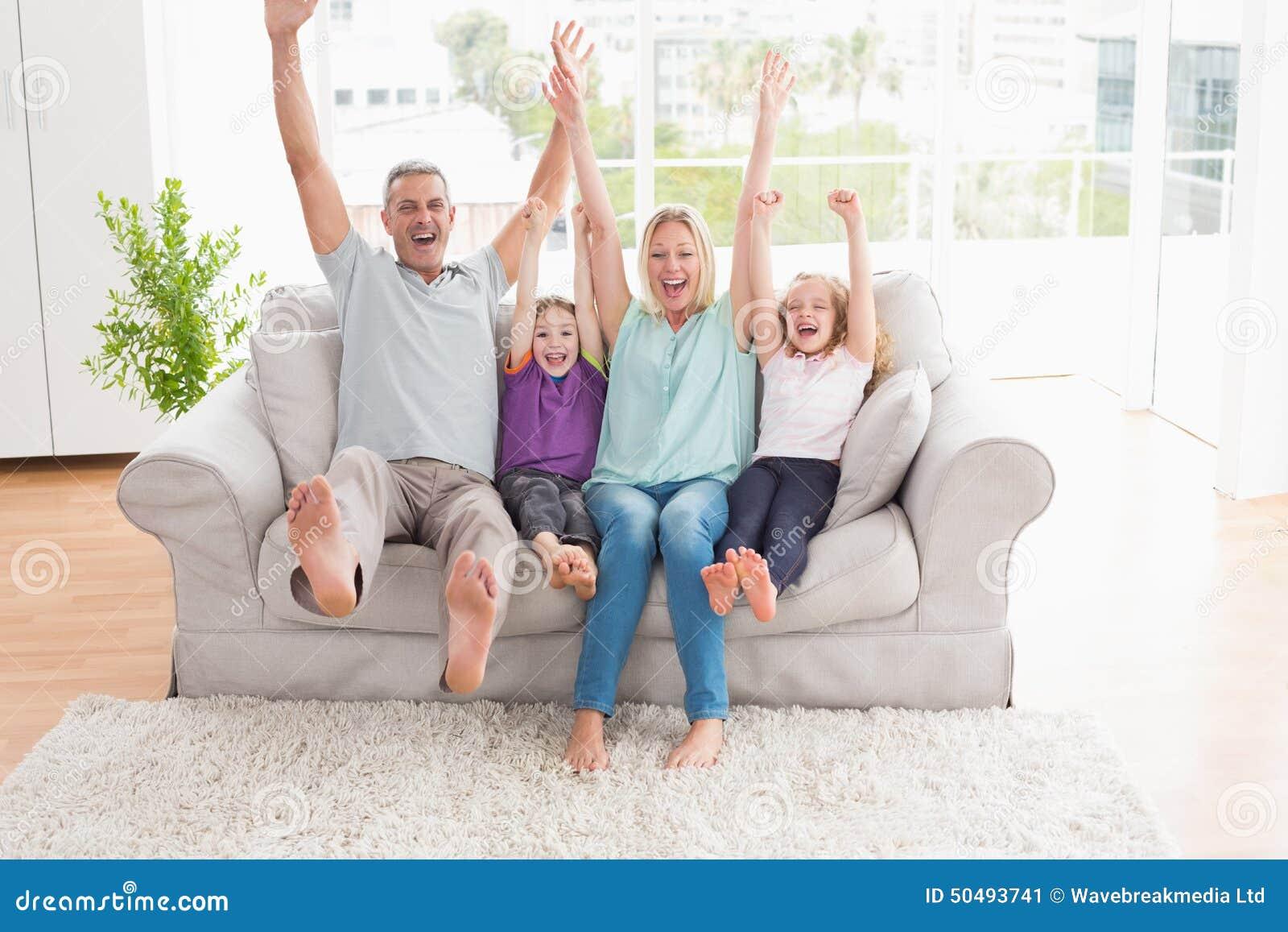 Família de quatro pessoas com assento levantado braços no sofá