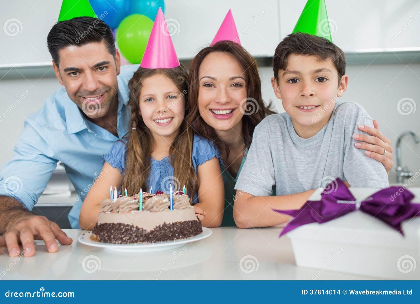 Família de quatro pessoas com bolo e presentes na festa de anos
