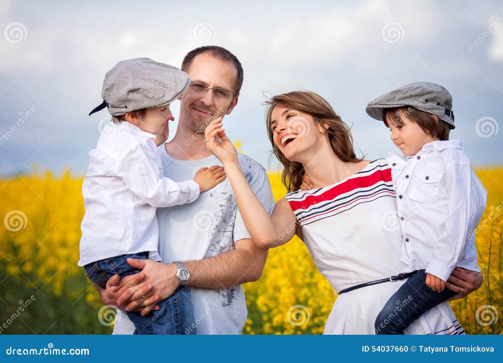 Família de quatro pessoas, mãe, pai e dois meninos, em uma violação de semente oleaginosa f