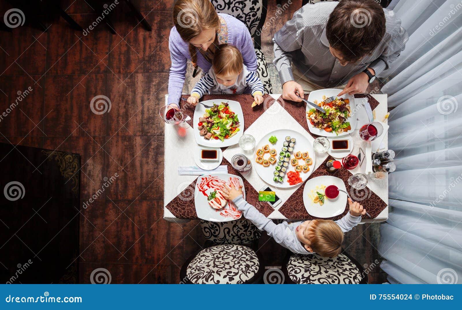 Família de quatro pessoas que tem a refeição em um restaurante