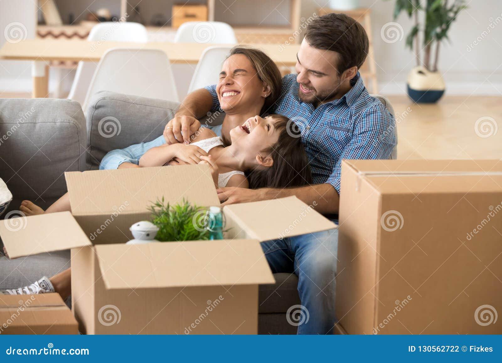 Família de riso para passar o tempo que tem o divertimento na casa nova