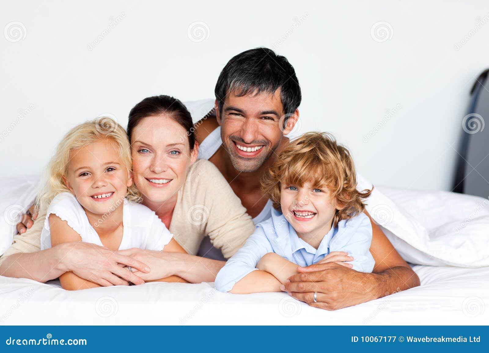 Família de sorriso junto na cama