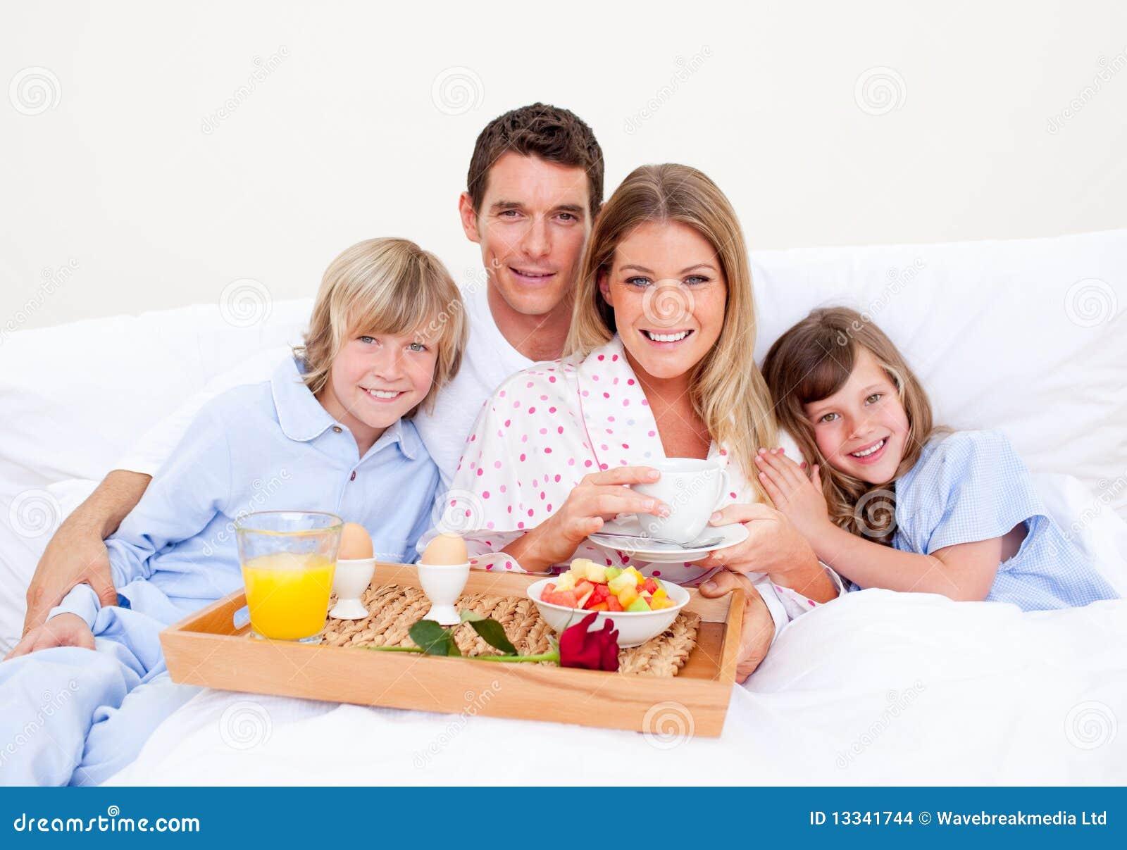 Família de sorriso que come o pequeno almoço sentar-se na cama