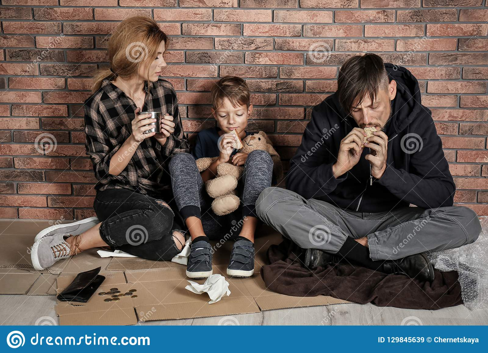 Família desabrigada pobre que senta-se no assoalho