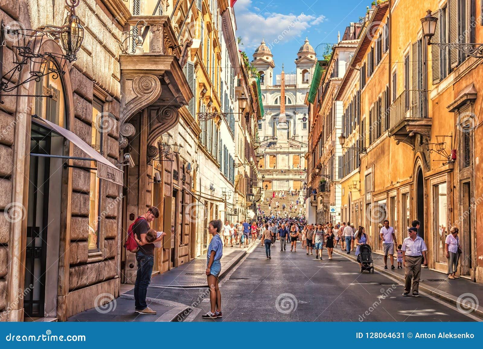 Família dos turistas dentro através do dei Condotti, de uma rua que conduzem a Praça di Spagna e das etapas espanholas