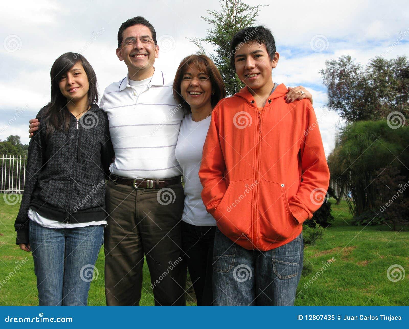 A família está na grama de encontro à casa