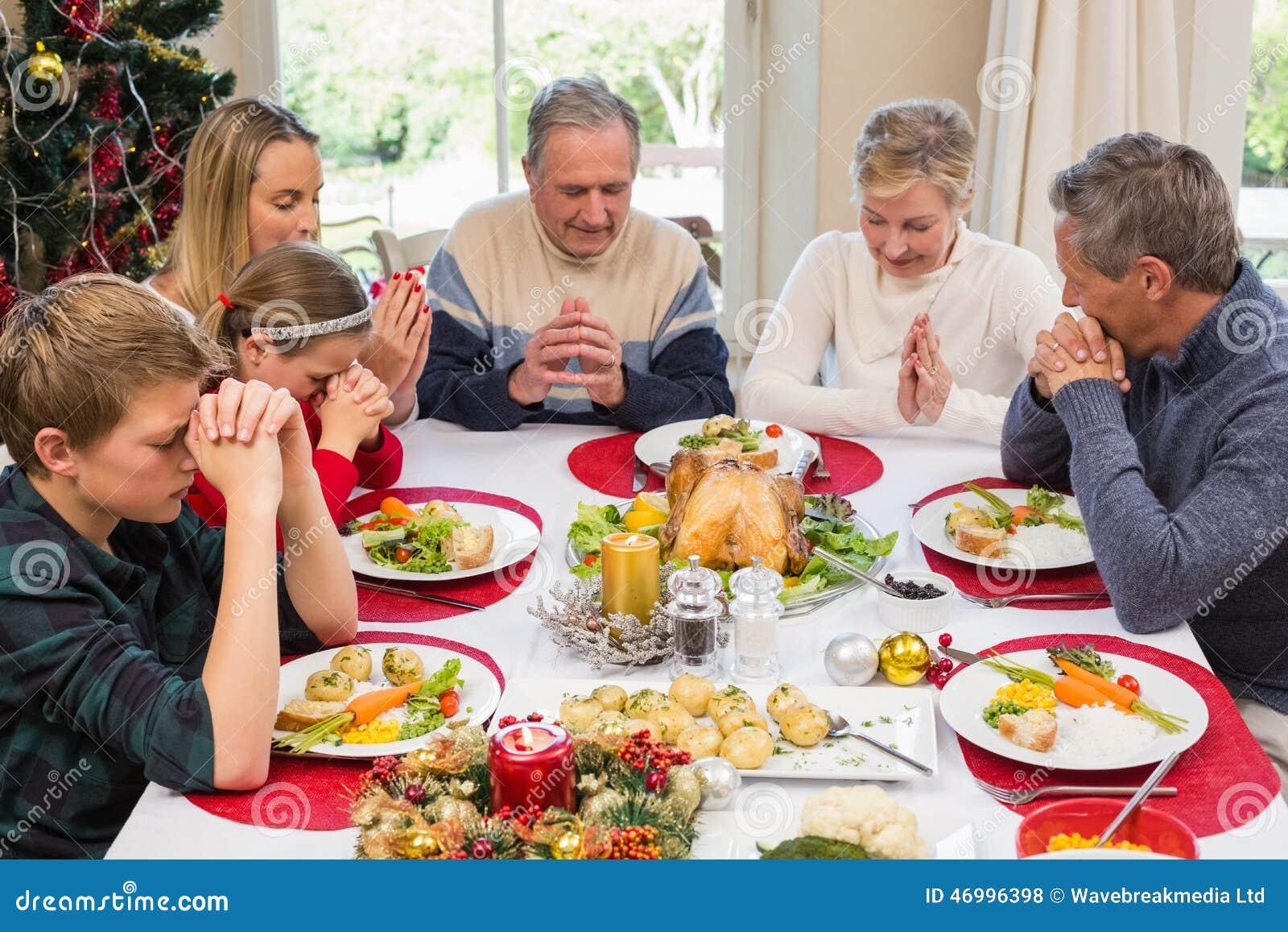Família extensa que diz a benevolência antes do jantar de Natal