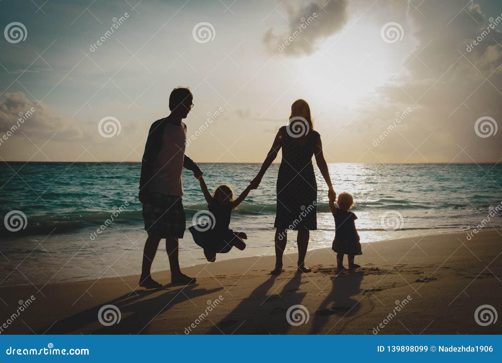 Família feliz com as crianças no jogo na praia do por do sol