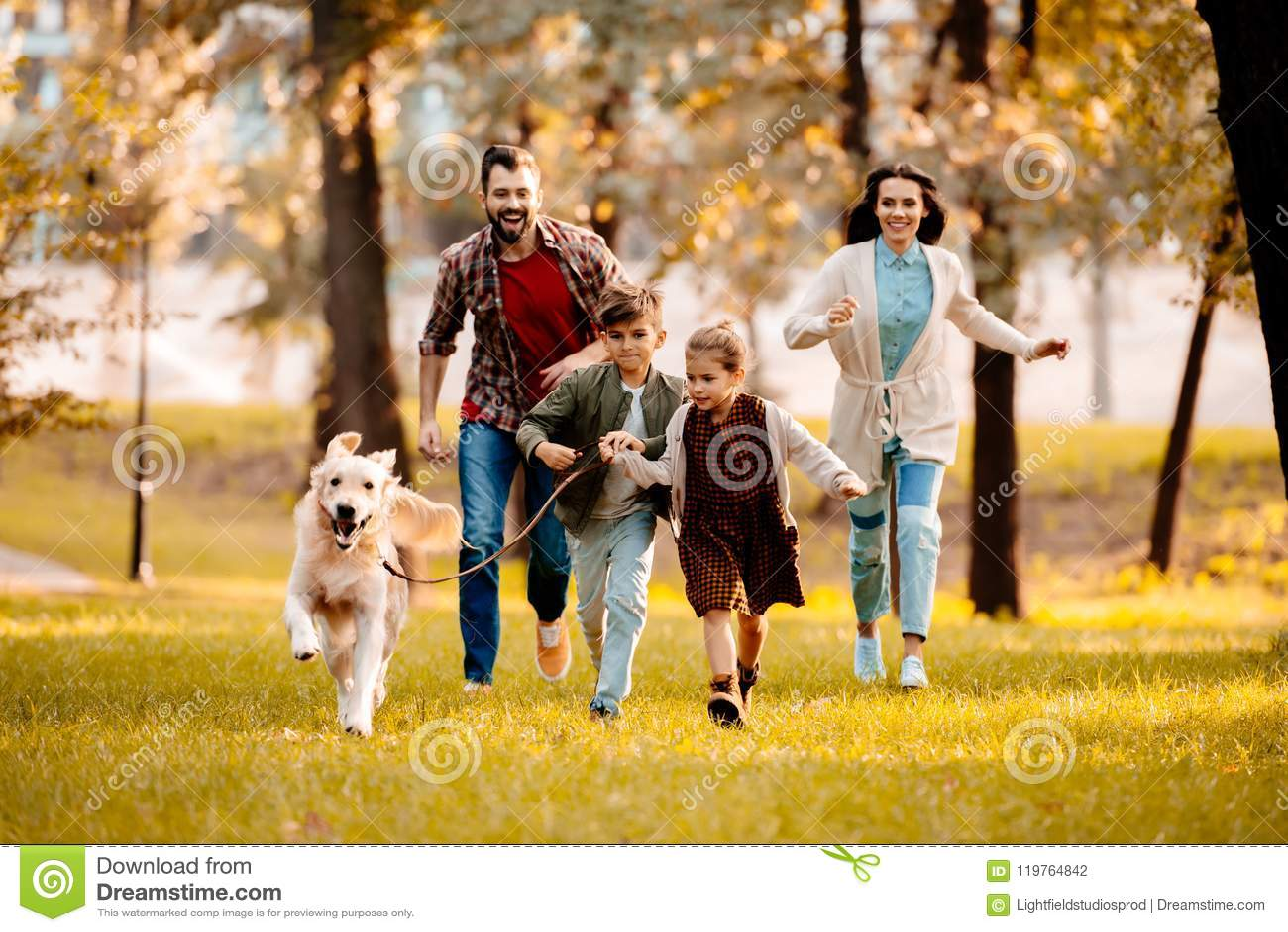 Família feliz com as duas crianças que correm após um cão junto