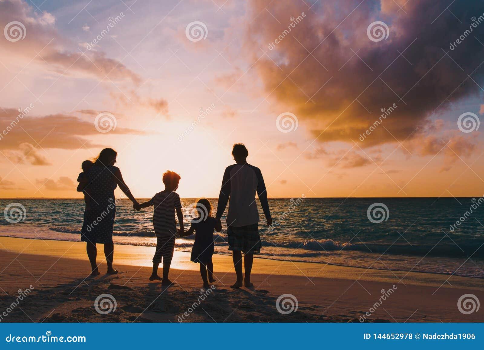 A família feliz com crianças da árvore anda na praia do por do sol