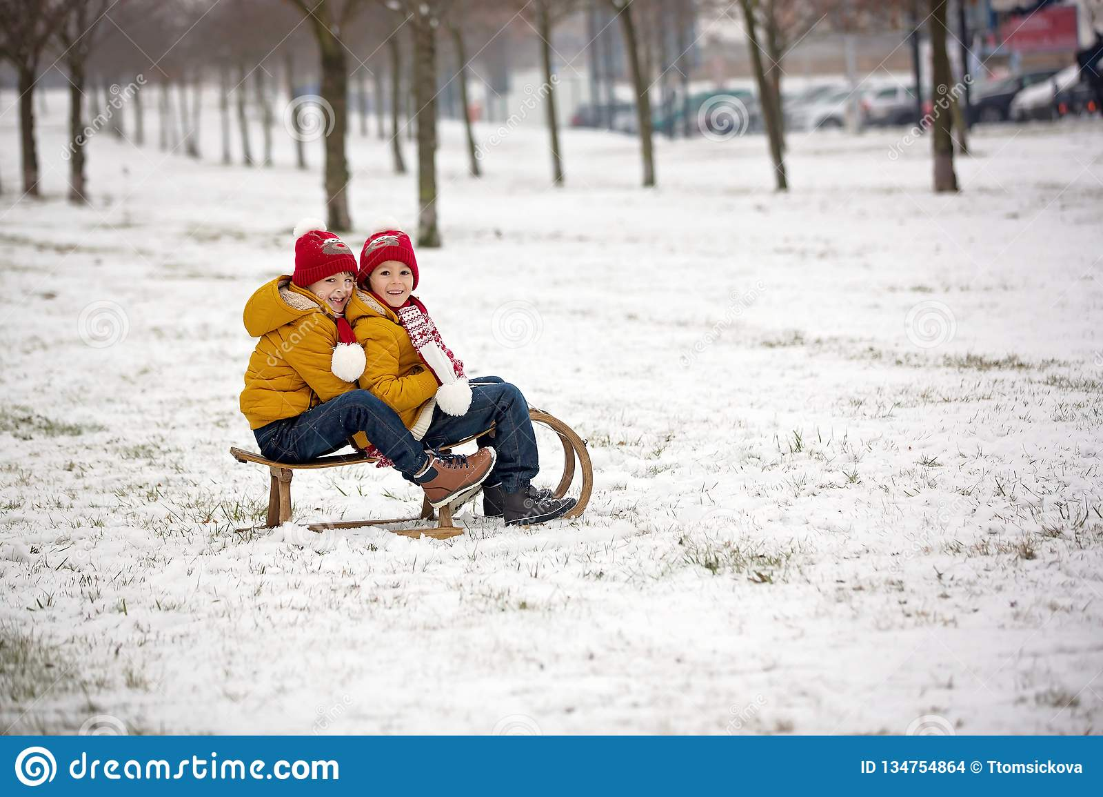 Família feliz com crianças, tendo o divertimento exterior na neve no Natal, jogando com pequeno trenó