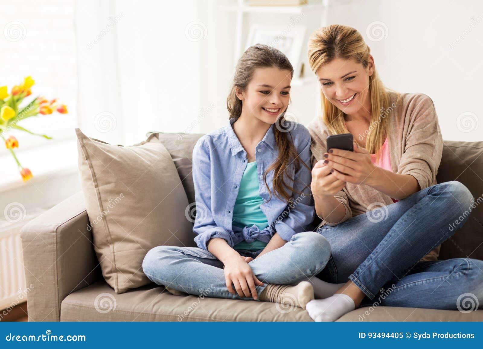 Família feliz com smartphone em casa
